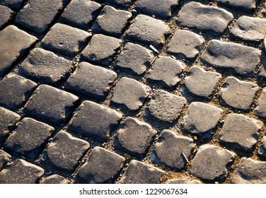 Square lined with cobblestone or stone pavement, walkway or road. The surface of rough stones and rough. The cobbles have a mottled pattern and texture.