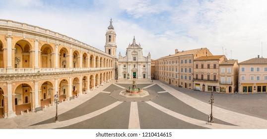 Square of Loreto, Basilica della Santa Casa in sunny day, portico to the side, people in the square in Loreto in Ancona, Italy