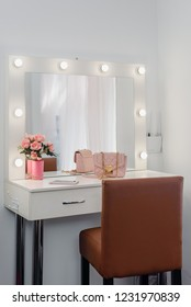 Square mirror with lamps and rose bouquet on visagist working place