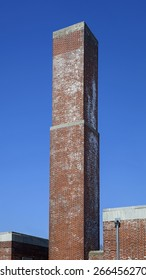 square old Industrial chimney made from red bricks against the blue sky