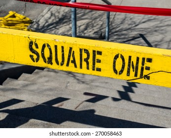 """Square One Yellow Sign. A yellow barricade with the words """"square one"""" written on it in black."""