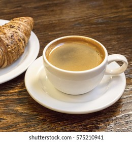 A square photo of cup of dark coffee with cereal croissant