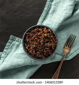 A square photo of wild black rice, shot from the top on a black background with a fork and copy space