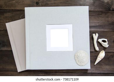 Square photobook albums in linen hardcover with passepartout frame and empty area for your text, photo or design on the wooden background and shell decor