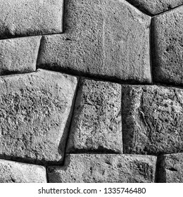 Square photograph in black and white of an Inca Wall in the archaeological ruin of Sacsayhuaman in Cusco, Peru.
