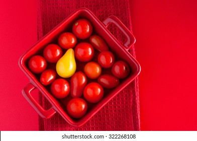 Square plate with cherry tomatoes on a red table with a kitchen towel, top view. Can be used as an illustration of an idea of difference, standing outside the crowd. Copy space, top view, flat lay