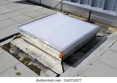 Square plexiglass skylight on a terrace on a construction site