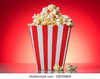 Square red and white striped popcorn box on a bright red background