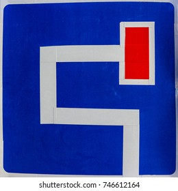 Square road sign. On a blue background intricate road and a dead-end. Complex, complicated situation, bad route. Sunlight.