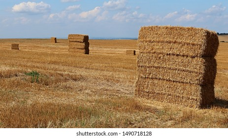 Square shaped hay bales stacked in number of three on harvested wheat field, drying on summer sun, blue skies with some clouds in background.