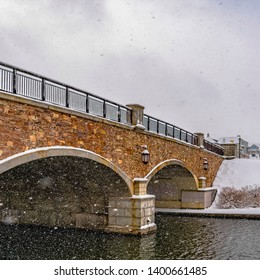 Square Stone arched bridge with lamps over a lake during winter in Daybreak Utah