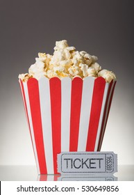 The square striped box with popcorn and movie ticket on a gray background