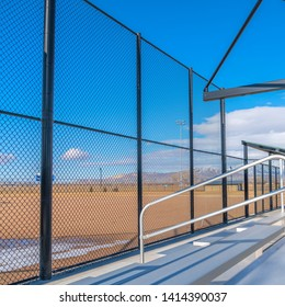 Square Sunlit bleachers overlooking a vast sports field on the other side of the fence