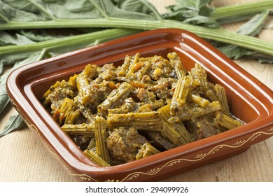 Square tajine with meat and cardoon and fresh cardoon on the background
