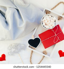 Square Top view flat lay sill life romantic composition. Hot cacao coffee chocolate with marshmallows mug red gift hearts tray in bed. Concept birthday holiday cozy warm home morning natural light