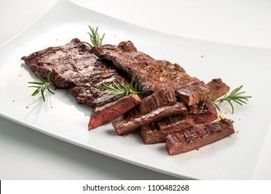 Square white plate of sliced skirt steak and rosemary