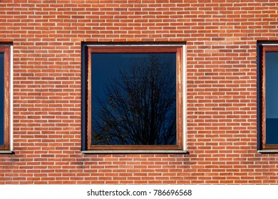Square window with hardwood frame in a red brick facade