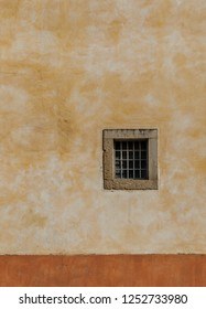 Square window on old building facade ocre painted
