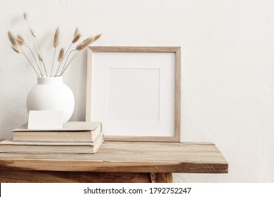 Square wooden frame mockup on vintage bench, table. Modern white ceramic vase with dry grass, books and busines card. White wall background. Scandinavian interior. - Shutterstock ID 1792752247