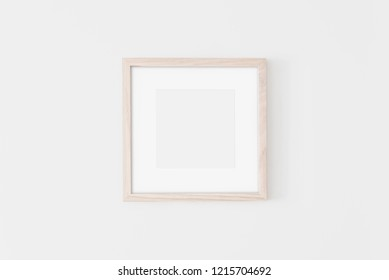 Square Wooden frame mockup with passe-partout on white wall. Poster mockup. Clean, modern, minimal frame. Empty fra.me Indoor interior, show text or product