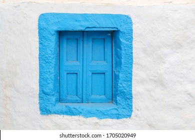 A square wooden window in blue against a white stone wall