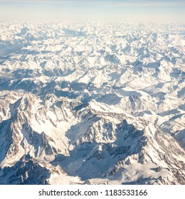 Squared aerial image of snowy alpine mountains seen from a plane flying above