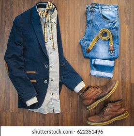 Squared flat lay of mens casual clothes set such as blue suit with patches, jeans, checkered bowtie, belt and shoes on brown wooden background. Top view.