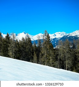 Squared image of empty ski mountain snow slope landscape with beautiful coniferous forest and blue sky. Kronplatz, Dolomites, South Tyrol, Italy.