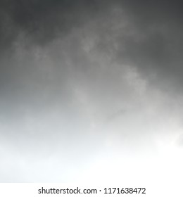 Squared image of moody dark clouds, white copy space at the bottom. Gradient from top to bottom.