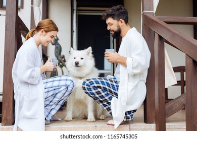 Squared pajamas. Happy beaming couple wearing squared pajamas drinking delicious morning coffee