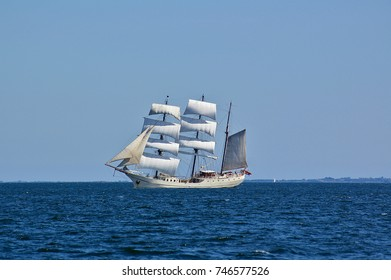 Square-rigged white sailing ship at sea with a distant shore in the far background