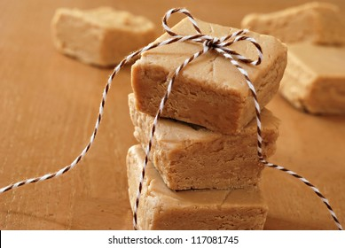 Squares of creamy peanut butter fudge stacked and tied with festive bakers twine for holiday gift giving.  Macro with extremely shallow dof.