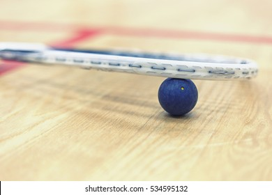 Squash ball between squash racket and floor on the court. Photo with toning and selective focus