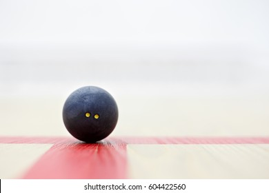 Squash ball on the court on the red line. Photo with selective focus and copy space