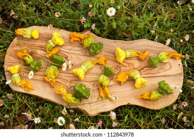 squash blossoms on wooden board with grass background