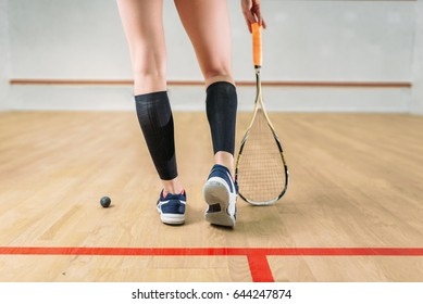 Squash game female player legs, racket and ball
