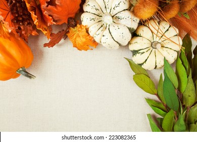 Squash and imitation leaves, berries and wild flowers form a border and background on woven fabric background with copy space for fall & Thanksgiving themes.