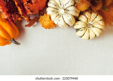 Squash and imitation maple leaves and wild flowers for fall & Thanksgiving themes. Fabric / canvas textured background.
