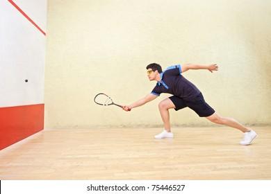 A squash player hiting a ball in a squash court