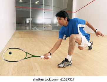 Squash player hiting a drop shot in a squash court.