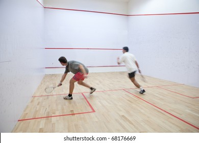 Squash players in action on a squash court (motion blurred image; color toned image)