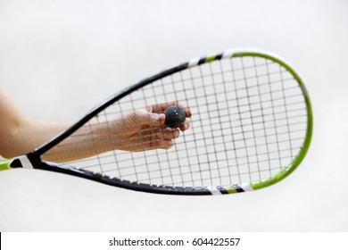 squash racket and ball in male hands. Racquetball equipment. Photo with selective focus