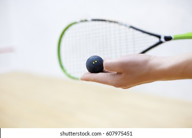 squash racket and ball in man's hands. Racquetball equipment. Photo with selective focus