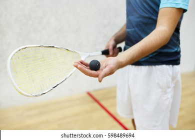 squash racket and ball in men's hand. Racquetball equipment. Photo with selective focus