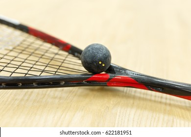 squash racket and ball on the floor. Closeup of racquetball equipment on the court. Photo with selective focus