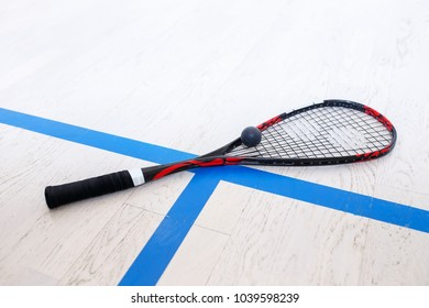 squash racket and ball on the wooden floor. Racquetball equipment on the court. Photo with selective focus