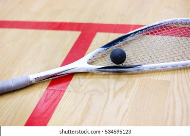 squash racket and ball on the wooden background. Photo with selective focus