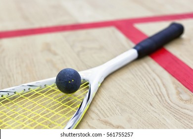squash racket and ball on the wooden floor. Racquetball equipment on the court next to a red line. Photo with selective focus