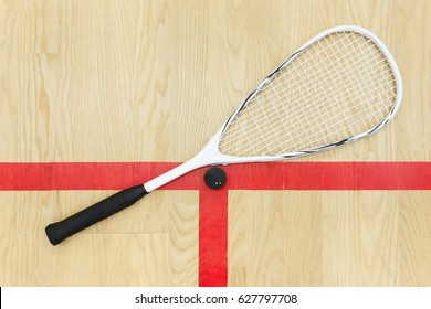 squash racket and ball on the wooden background view from above . Racquetball equipment on the court near red line