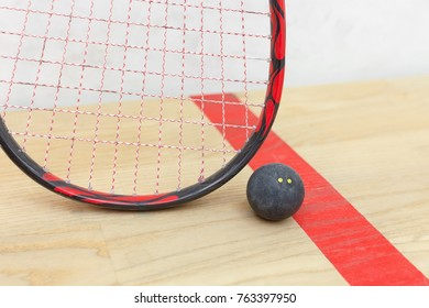 squash racket and ball on the wooden floor. Closeup racquetball equipment on the court near red line. Photo with selective focus